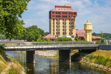 VUKOVAR, CROATIA - MAY 14, 2018 : View of pedestrian bridge of Jean Michel Nicolier with abandoned hotel Dunav in the background in Vukovar, Croatia.