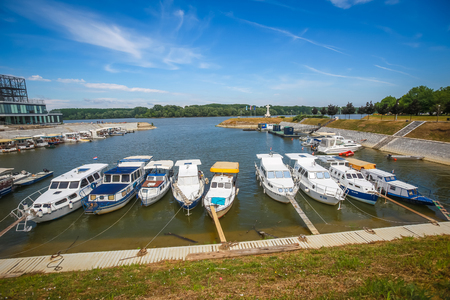VUKOVAR, CROATIA - MAY 14, 2018 : A view of boats moored on the coast of the river Dunav with  the cross in memory of croatian war defenders in the background in Vukovar, Croatia.