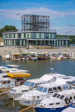 VUKOVAR, CROATIA - MAY 14, 2018 : A view of boats moored on the coast of the river Dunav in front of a contemporary building in Vukovar, Croatia.