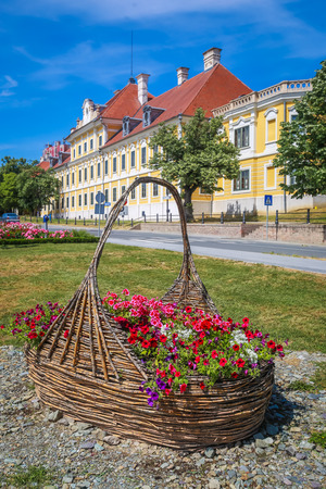 View of a large straw basket with flowers in a park with the City museum located in the Eltz castle in the background  in Vukovar, Croatia.