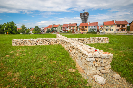 A view of the votive stone cross as a symbol of the sacrifice and suffering of the city during the Independence war with the Vukovar water tower in the background in Vukovar, Croatia.
