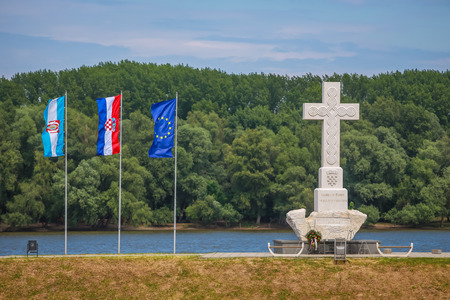 A view of the cross monument that says To victims of war for free Croatia in memory of croatian war defenders with flags hoisted next to it in Vukovar, Croatia.