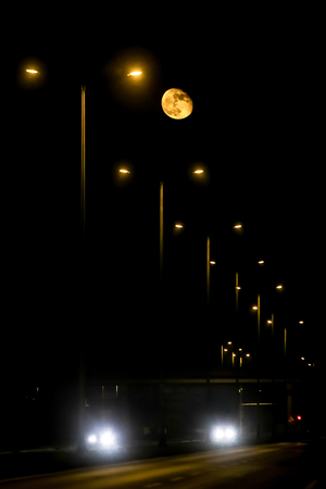 A view of full moon above the highway at night.