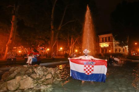 ZAGREB, CROATIA - JULY 11, 2018 : Croatian football fans celebrating victory of 2:1 Croatia vs England in semi finales Fifa World cup 2018 in water fountain on Zrinjevac park in Zagreb, Croatia.