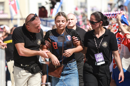 ZAGREB, CROATIA - JULY 16, 2018 : Croatia National Team welcome home celebration for 2nd place on Fifa World Cup 2018.Security guards pulled out dehydrated people from the crowd on Ban Jelacic square.