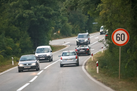 Omisalj, Croatia - August 1th, 2018 : Traffic on a two way road with 60km/h speed restriction sign on the island of Krk in Omisalj, Croatia. Editorial