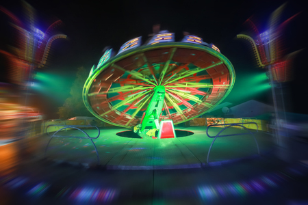 An illuminated rotating circular device in an amusement park with zoom in effect.