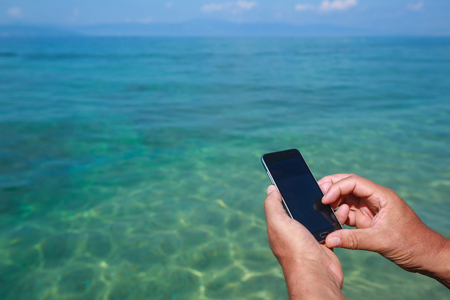 A man holding smartphone while sitting on the seaside pier. Stock Photo