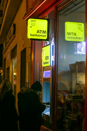 Zagreb, Croatia - 29th, December 2018 : People picking up money on the Atm machine on the street during night. Editorial