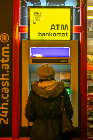Zagreb, Croatia - 29th, December 2018 : People picking up money on the Atm machine on the street during night. Stock Photo - 118947924