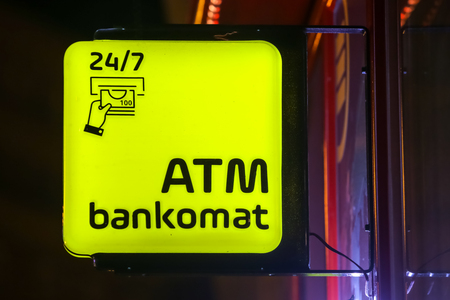 Close up of Atm machine yellow sign on the street during night.
