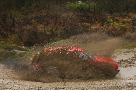Red rally car driving thru the mud during the race