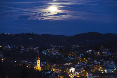 Church in the village with full moon at night