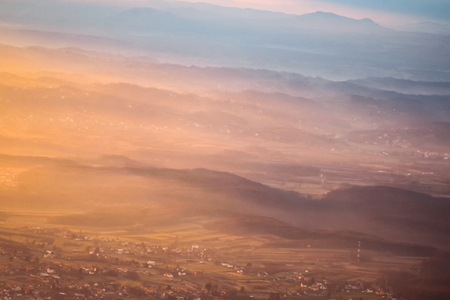 A view of the sunset over the village and mountain peaks. Stock Photo - 118985576