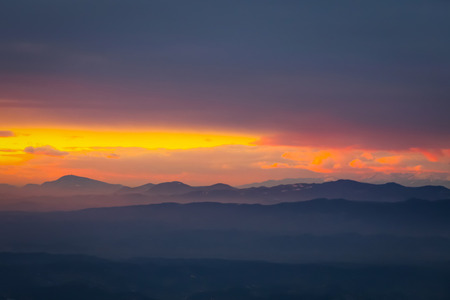 A view of the sunset over the village and mountain peaks.