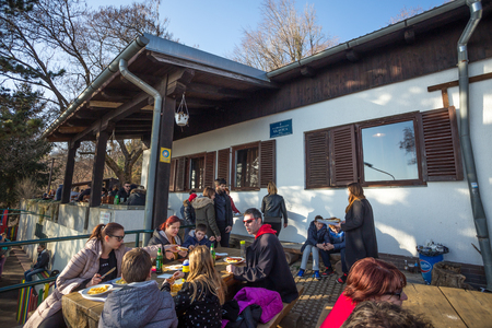 Zagreb, Croatia - February 17, 2019 : A large group of people sitting at tables, drinking and eating at the Glavica mountain hut on Medvednica mountain. Stock Photo - 118948153