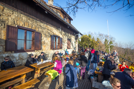 Zagreb, Croatia - February 17, 2019 : A large group of people sitting at tables, drinking and eating at the Glavica mountain hut on Medvednica mountain.