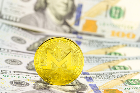 Cryptocurrency monero displayed on a heap of one hundred dollar bills. Stock Photo
