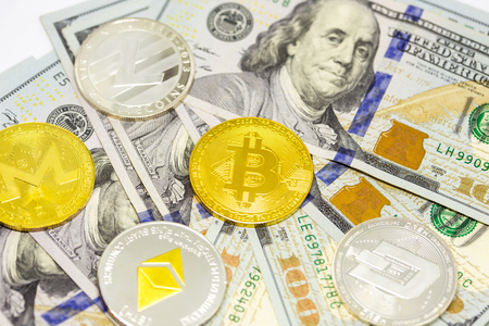 Cryptocurrency bitcoin, dash, litecoin, ethereum, monerocoins displayed on a heap of one hundred dollar bills.