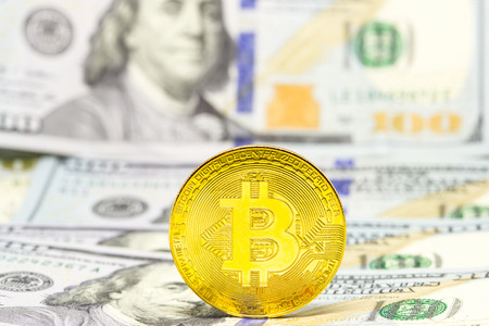 Cryptocurrency bitcoin displayed on a heap of one hundred dollar bills.