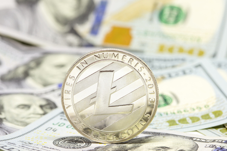 Cryptocurrency litecoin displayed on a heap of one hundred dollar bills. Stock Photo