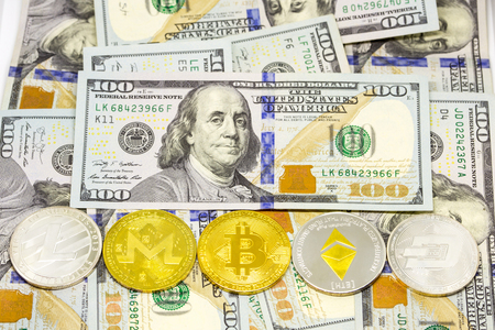 Cryptocurrency bitcoin, dash, litecoin, ethereum, monerocoins displayed lined up on a heap of one hundred dollar bills.