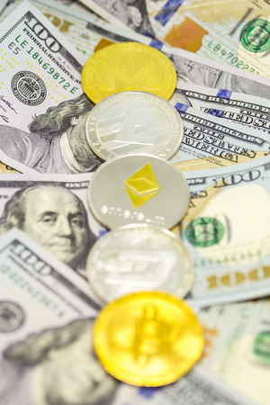 Lined up cryptocurrency coins displayed on a heap of one hundred dollar bills with focus on litecoin coin.