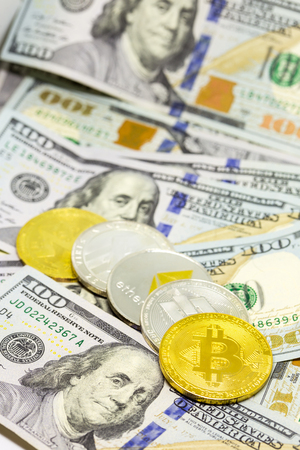 Lined up cryptocurrency coins displayed on a heap of one hundred dollar bills with focus on bitcon coin. Stock Photo