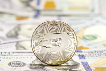 Cryptocurrency dash coin displayed on a heap of one hundred dollar bills. Stock Photo