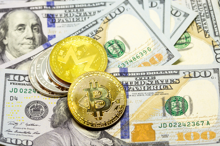Pile of cryptocurrency coins with bitcoin as main coin displayed on a heap of one hundred dollar bills.
