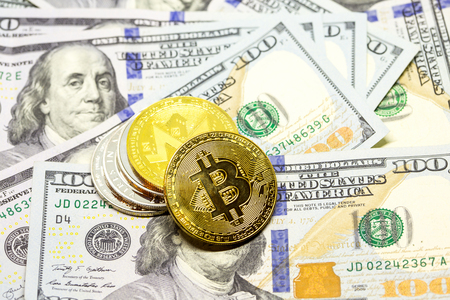 Pile of cryptocurrency coins with bitcoin as first coin displayed on a heap of one hundred dollar bills. Stock Photo