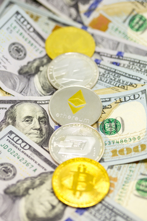 Lined up cryptocurrency coins displayed on a heap of one hundred dollar bills with focus on ethereum coin.