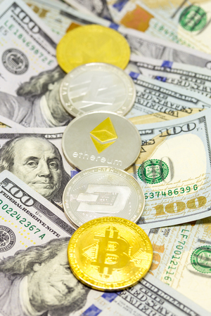Lined up cryptocurrency coins displayed on a heap of one hundred dollar bills with focus on dash coin.