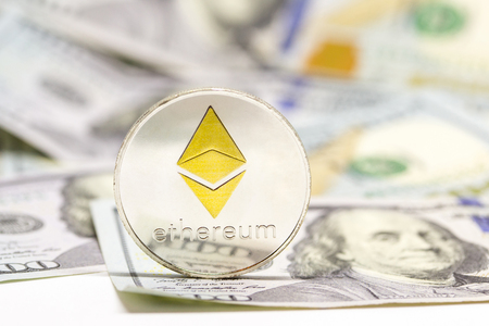 Cryptocurrency ethereum coin displayed on a one hundred dollar bills.