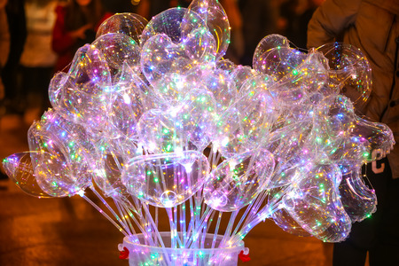 The group of illuminating balloons with led diodes in the street during the night.
