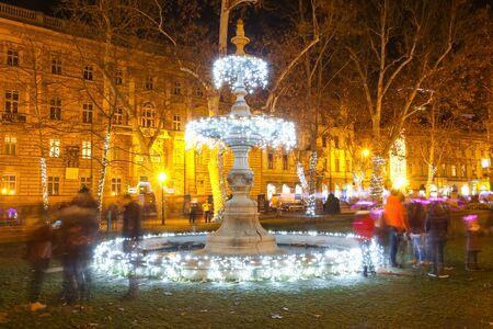 Advent time in city center of Zagreb, Croatia. The illuminated fountain in ornate Zrinjevac park with blurry people around it.