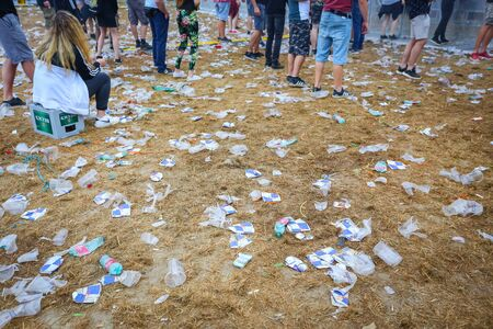 Brezje, Croatia - 20th July, 2019 : Detail of plastic cups and garbage on the floor after whole night of partying on the Forestland, ultimate forest electronic music festival located in Brezje, Croatia.