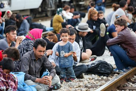 Dugo Selo, Croatia - September 17, 2015 : A group of Syrian refugees sitting on the train tracks after arriving from Serbia and waiting for the buses to continue to the northern european countries.