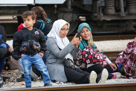Dugo Selo,Croatia - September 17, 2015 : Syrian woman photographing and sitting on the train tracks after arriving from Serbia and waiting for the buses to continue to the northern european countries. Redactioneel
