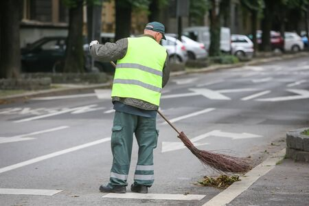 Garbage man brooming the leaves on the street of the city. Stock Photo