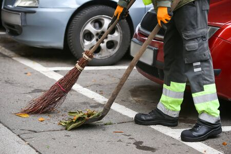 Garbage man brooming the leaves on the street of the city. Banco de Imagens