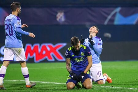 Zagreb, Croatia - December 11, 2019 : Dinamo Zagreb vs Manchester City, UEFA Champions League. Petar Stojanovic on his knees while Philip Walter Foden celebrates after scoring his goal for 1-4.