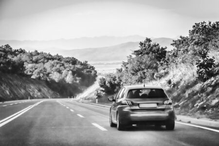 Rear view of a car driving on the two way road with landscape of Gorski Kotar in Croatia, in black and white.