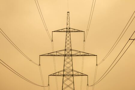 Silhouette of electric transmission tower, high voltage pole at cloudy day.