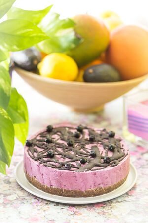 Pink raw vegan cake with cashew nuts and forest fruit topped with raw vegan chocolate with the plant and fruit basket in the background. 版權商用圖片