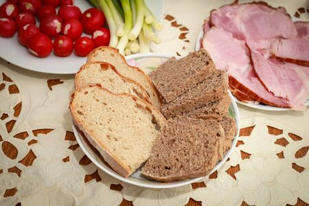 Traditional Easter breakfast, slices of bread on the plate at the table.