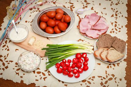 Traditional Easter breakfast, painted boiled chicken eggs, young onions, radishes, grated horseradish, sliced cooked ham, slices of bread, sauce and French salad on the table with Easter decoration.