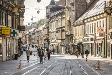 Zagreb, Croatia - 15 April, 2020 : People walking on the Ilica street that is blocked with police tapes and direction ban signs due to a major earthquake that damaged the city in Zagreb, Croatia.