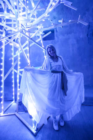 Zagreb, Croatia - 19 March, 2017 : Festival of lights in Zagreb, Croatia. Dressed girl as a fairy in a lighted tunnel Gric with lighted colorful wood shaped sculpture in the center of Zagreb.