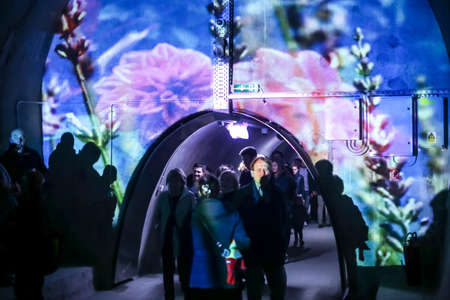 Zagreb, Croatia - 19 March, 2017 : Festival of lights in Zagreb, Croatia. People walking through a lighted tunnel Gric with illuminated colorful pictures on the wall in the center of Zagreb.